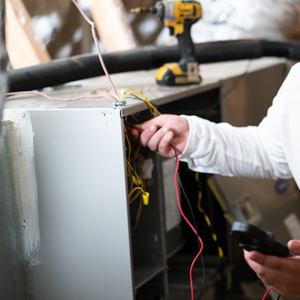 One of our experienced technicians checks this furnace's electrical current on a heating repair call.