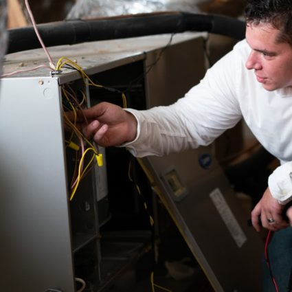 As part of a heating service call, our technician works on this furnace, located in the home's attic.