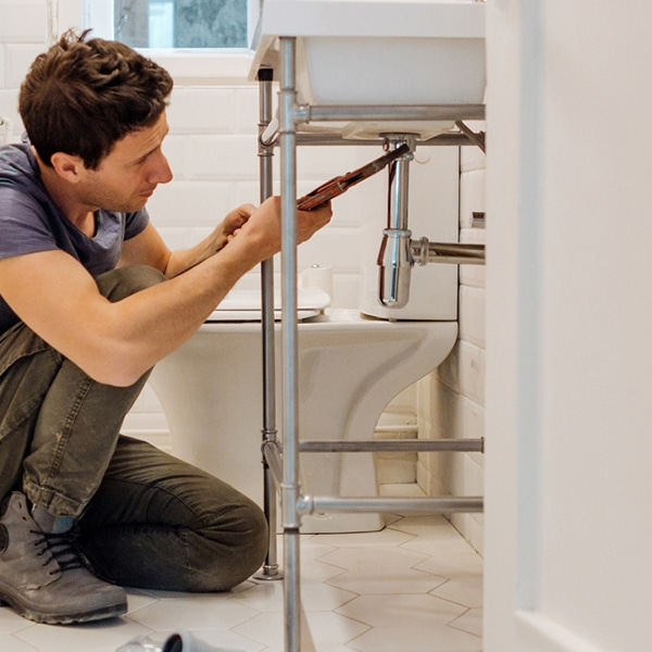 A plumber tightens a drain underneath this bathroom sink, ensuring that it will no longer leak and flood this bathroom.