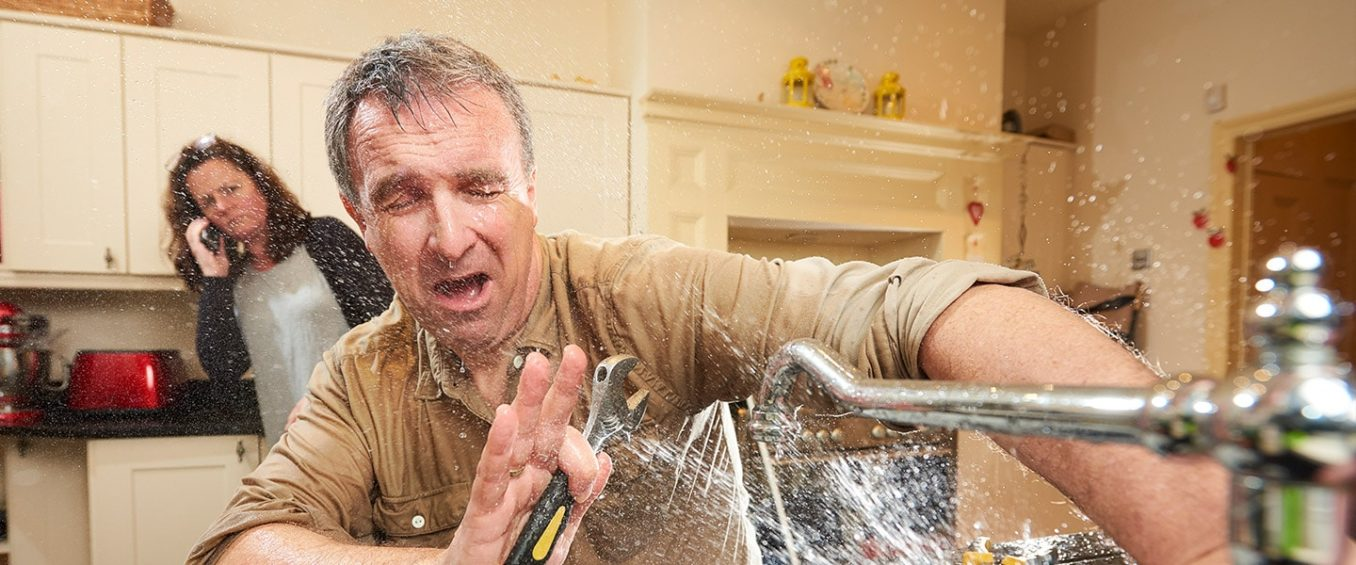 A homeowner trying to fix their own sink faucet gets a splash of cold water to his face, as his spouse calls in an emergency plumber.