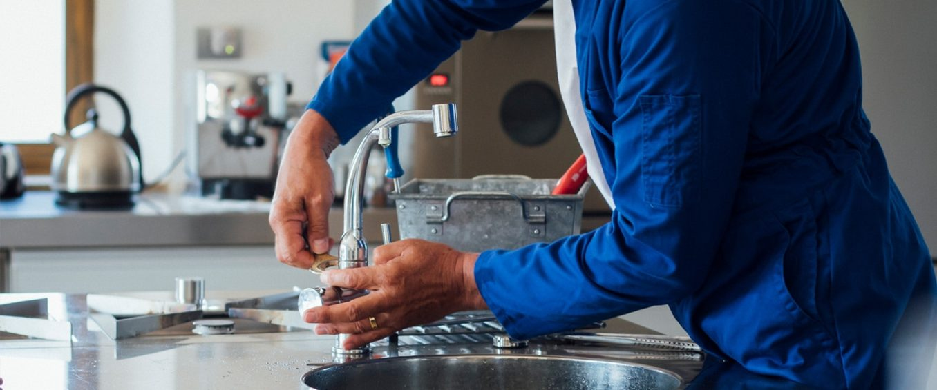 Wrapping up installation, one of our plumbers tightens the kitchen sink faucet and handles.