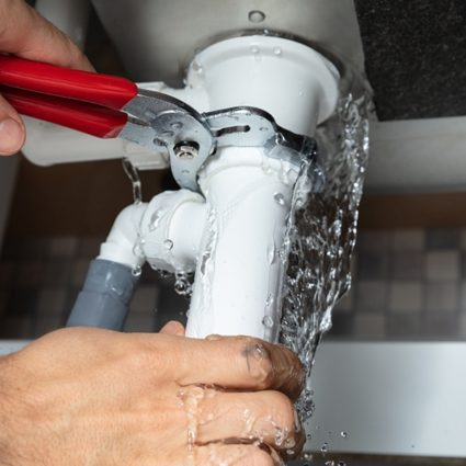 Water pours out from underneath a sink as our plumber works quickly to fix a leaking pipe.