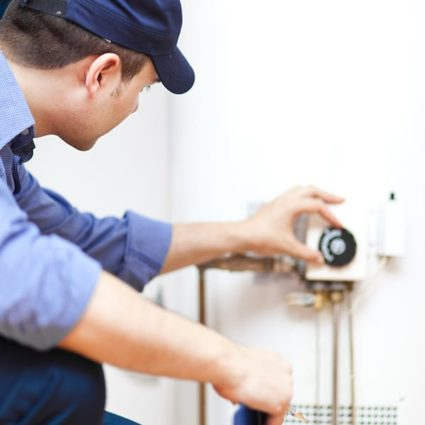 Our plumber adjusts the temperature dial on a water heater, setting it to the ideal temperature for efficiency and comfort.